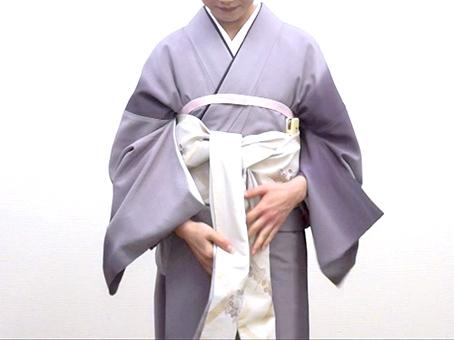 【1】 たれの柄止まりを右身八つ口で決め、胴に二巻きして手先結び上げをします。